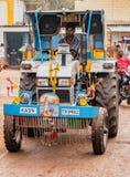 Mann fährt den Traktor, der mit Girlanden und enormen Sprechern verziert wird Stockbild