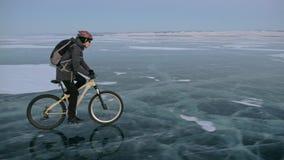 Mann fährt Fahrrad auf Eis Der Radfahrer wird in in einer Jacke, einem Rucksack und einem Sturzhelm des Graus unten gekleidet Eis stock video footage