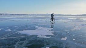 Mann fährt Fahrrad auf Eis Der Radfahrer wird in in einer Jacke, einem Rucksack und einem Sturzhelm des Graus unten gekleidet Eis stock video