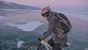 Mann fährt Fahrrad auf Eis Der Radfahrer wird in in einer Jacke, einem Rucksack und einem Sturzhelm des Graus unten gekleidet Eis stock footage