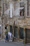 Mann färbt die Stangen des Fensters im Freien Lizenzfreies Stockfoto