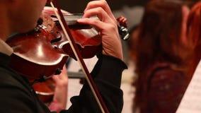 Mann führt das einzige Teil der ersten Geige durch, das am klassischen Konzert spielt stock footage