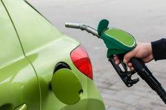 Mann füllt sein Auto mit einem Benzin auf stockbilder