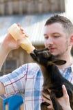 Mann füttert Ziege mit der Flasche Stockfoto