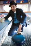 Mann in Fedora, das am Restaurant-Zählwerk sitzt Lizenzfreie Stockfotos