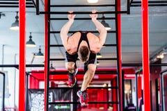 Mann an Freistil Gymnastik ausbildend in der Turnhalle Stockfotos
