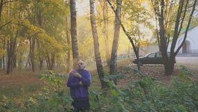 Mann friert im Herbstpark ein und wärmt Hände kalt stock video
