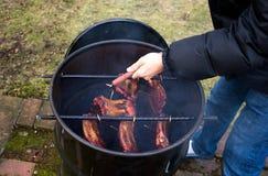 Mann gebratene Grillrauchschweinsrippchen Lizenzfreies Stockfoto