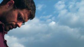 Mann gegen blauen Himmel stock video