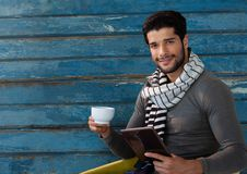 Mann gegen Holz mit warmem Schal und Schale und Tablette Stockfoto