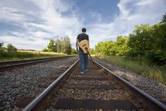 Mann-gehende Schienen-Straßen-Spuren mit Gitarre Lizenzfreie Stockfotografie