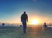 Mann geht auf den hölzernen Pier im Sonnenaufgang Der Kaibau Lizenzfreies Stockfoto
