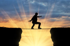Mann geht auf ein Drahtseil über einer Klippe Stockfotografie