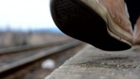 Mann geht entlang die Bahnen auf der Plattform stock video footage