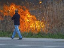 Mann geht entlang die Straße nahe einem Feuer lizenzfreies stockbild