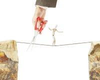 Mann geht entlang ein Seil, aber anderer schneidet es mit Scheren Stockfotos