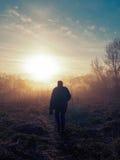 Mann geht gegen den Sonnenaufgang Stockbilder