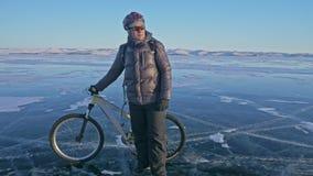 Mann geht neben Fahrrad auf dem Eis Der Radfahrer wird in in einer Jacke, einem Rucksack und einem Sturzhelm des Graus unten gekl stock footage