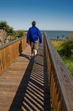 Mann geht in Richtung zum Ozean Stockbilder