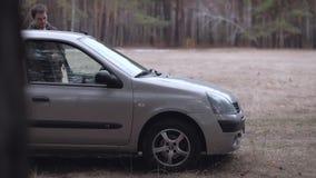Mann geht und sitzt im Auto stock footage
