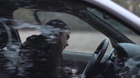 Mann geht und sitzt im Auto stock video