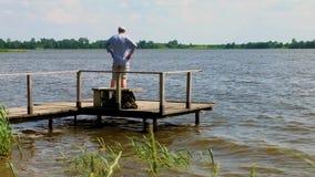 Mann geht und steht auf Pier am See im windigen Wetter stock video footage