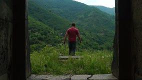 Mann geht vom Eingang der alten Kirche in den Bergen hinaus stock video