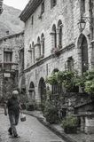 Mann geht vorbei in eine Straße des mittelalterlichen französischen Dorfs von Heilig-Guilhem-Le-Désert lizenzfreie stockbilder