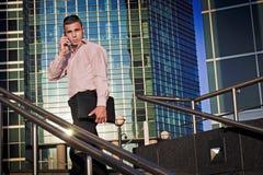 Mann geht zum Büro und spricht am Telefon Lizenzfreies Stockfoto