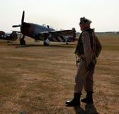 Mann gekleidet als amerikanischer Pilot des Zweiten Weltkrieges mit Kämpfer des Republik-Blitzes P47 lizenzfreie stockbilder