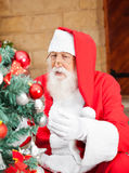 Mann gekleidet als Santa Claus Decorating Christmas Lizenzfreies Stockfoto
