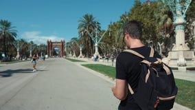 Mann genießt Stadtmarksteine in Barcelona und geht nahe Arc de Triomf stock video footage