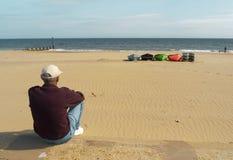 Mann gesetzt auf dem sandigen Strand, der heraus zum Meer anstarrt Lizenzfreie Stockfotos