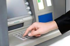 Mann gibt einen PIN-Code ein und nimmt Geld von einem ATM zurück Stockbild