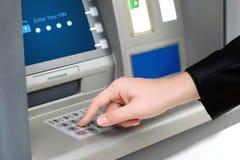 Mann gibt einen PIN-Code ein und nimmt Geld von einem ATM zurück Lizenzfreie Stockbilder