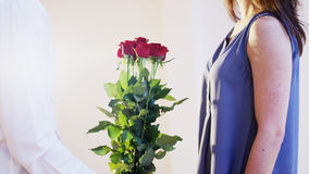 Mann gibt einer Frau einen Blumenstrauß von roten Rosen Lizenzfreies Stockbild