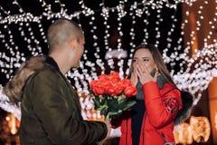 Mann gibt seinen Freundinblumenstrauß von Rosen nachts lizenzfreies stockfoto