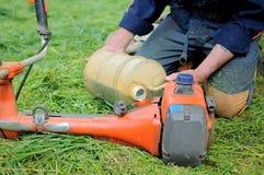 Mann gießt BrennstoffRasenmäher Lizenzfreies Stockfoto