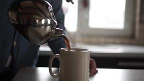 Mann gießt Kaffee in einen Becher stock video footage