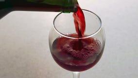Mann gießt Rotwein in das Glas, das auf Tabelle in der Küche steht stock footage