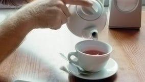 Mann gießt Tee von den Teekannenflecken und wischt Tabelle ab stock footage