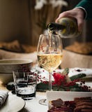 Mann gießt Weißwein in ein Glas Lizenzfreies Stockbild