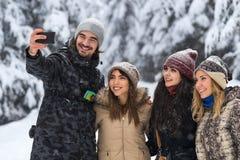 Mann-Griff-intelligente Telefon-Kamera, die Selfie-Foto-Freunden Lächeln-Schnee Forest Young People Group Outdoor nimmt Stockbild