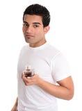Mann hält Aftershave oder Duft der Männer an stockfotos