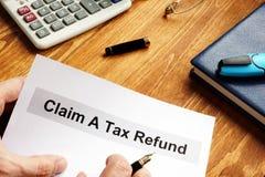 Mann hält behaupten Dokumente einer Steuerrückzahlung lizenzfreie stockfotografie