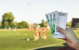 Mann hält eine Buchmacher ` s Karte und Geldeuros im Hintergrund eines Stadionsfußballspiels, Nahaufnahme lizenzfreies stockfoto