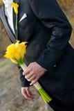 Mann hält einen Hochzeitsblumenstrauß an Stockfotos