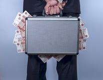 Mann hält einen Koffer voll vom Geld hinter der Rückseite Stockfoto