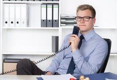 Mann hält einen Telefonhörer im Büro Stockfotografie