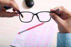 Mann hält Gläser in der Hand Bild der Maus, Bleistift und OMR bedecken lizenzfreies stockbild